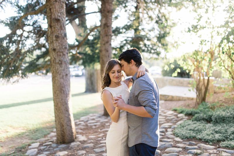 Husband and wife dancing in an outdoor location with trees surrounding them