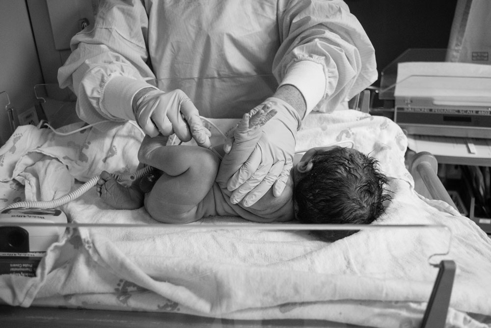 Birth photographer captures nurse taking newborn babies temperature
