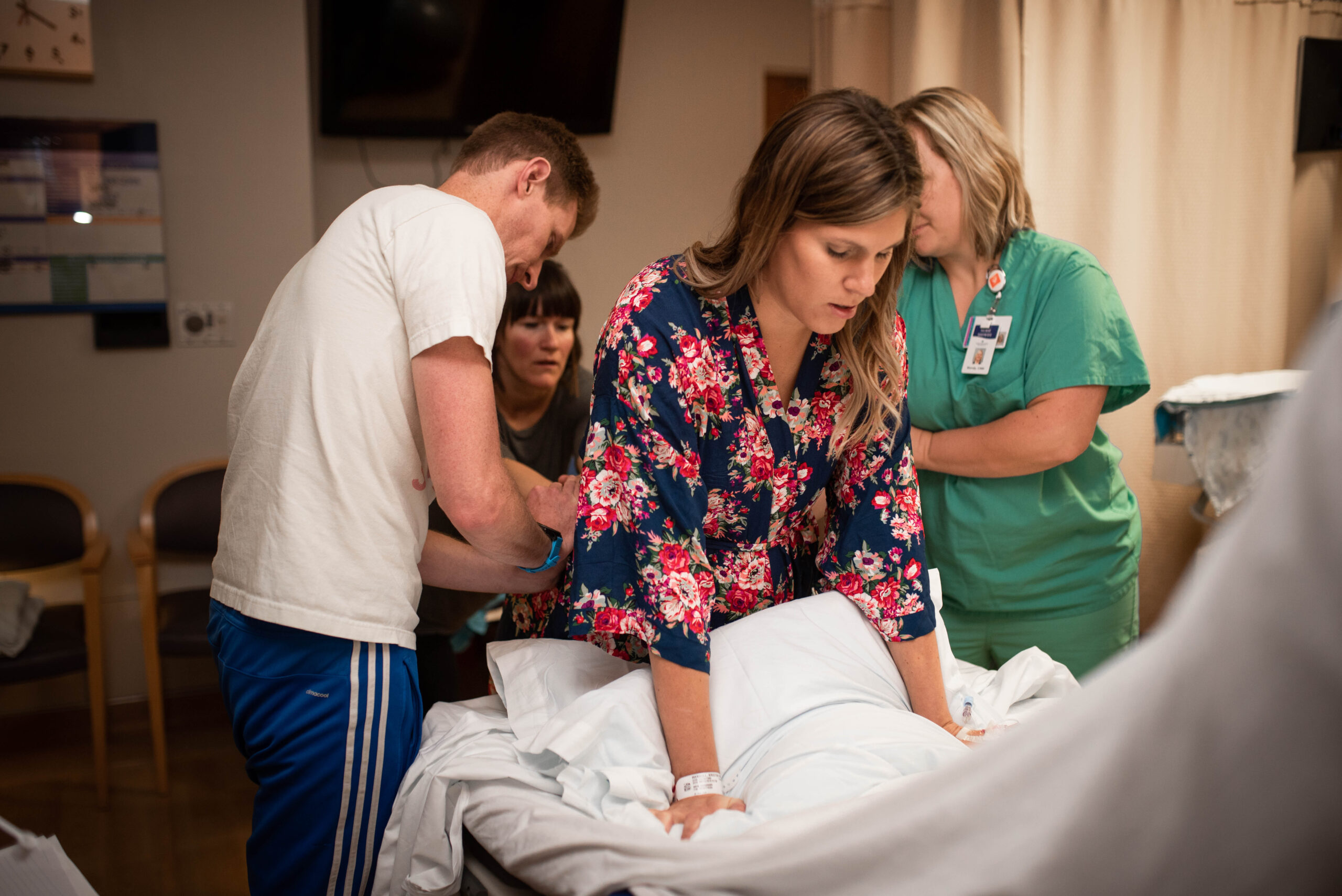 Utah mom in labor while husband, doula and midwife apply counter pressure on her hips