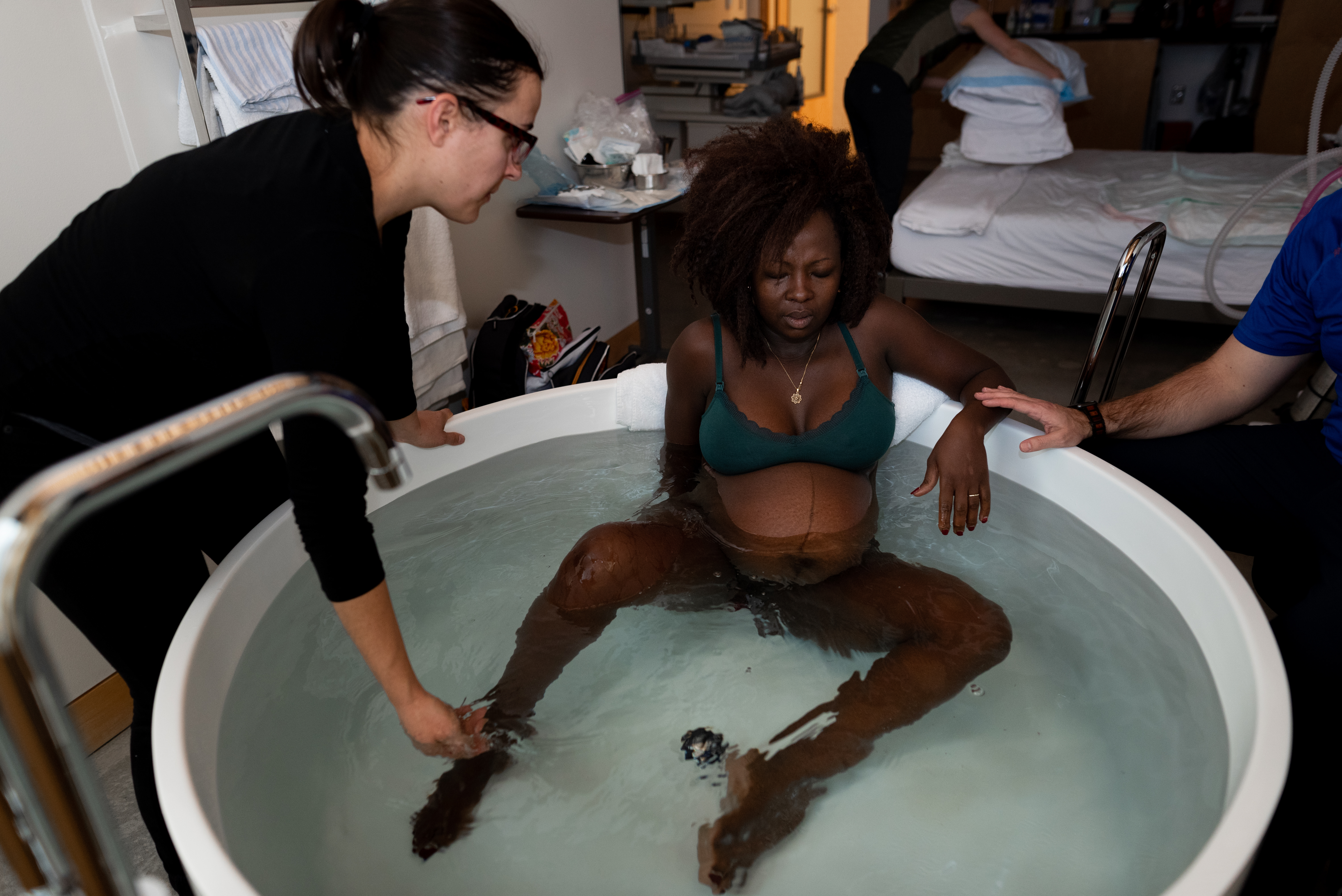 A doula supports a laboring mother during birth in a bathtub