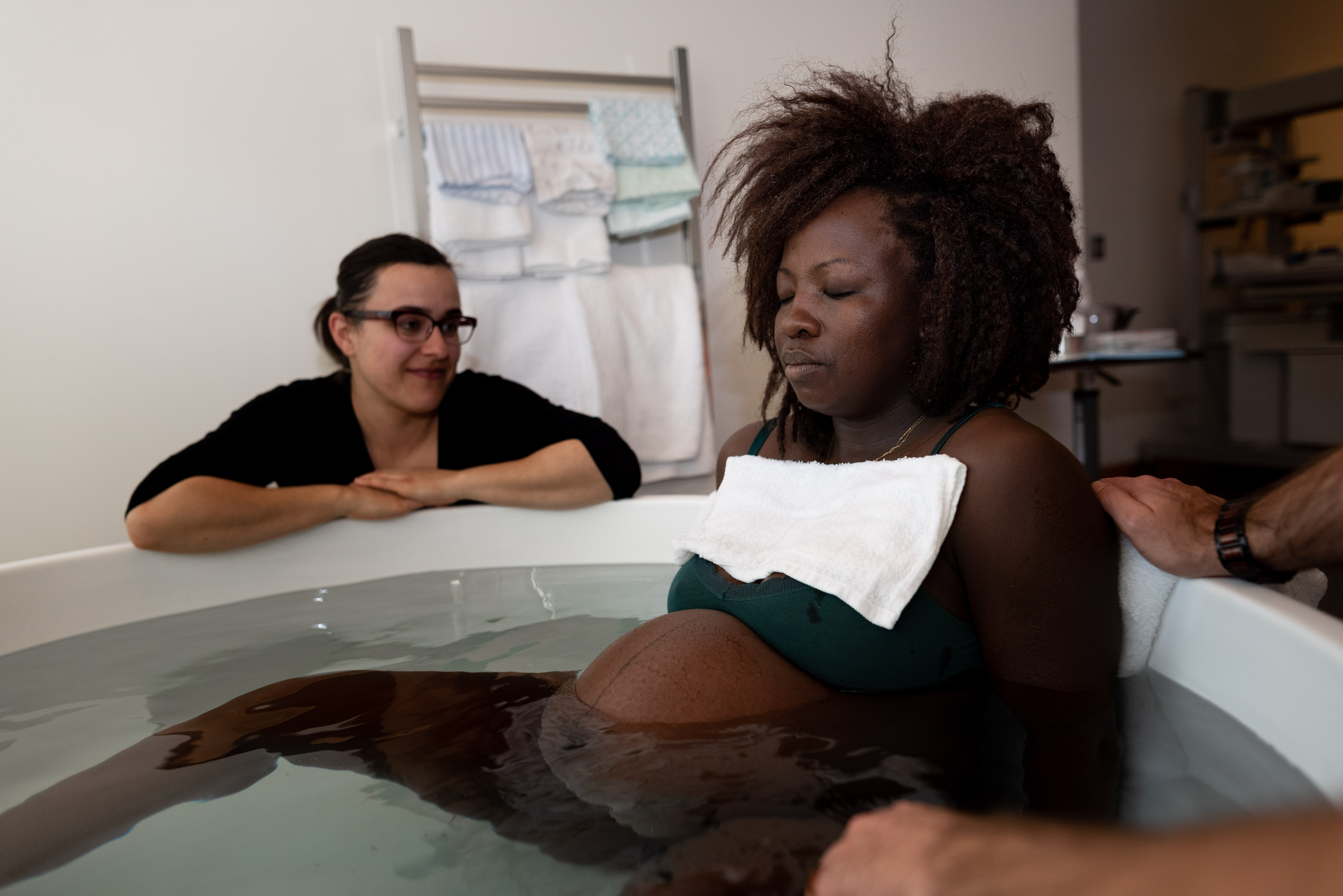 A mother sits in a bathtub with a doula by her side during a birth story