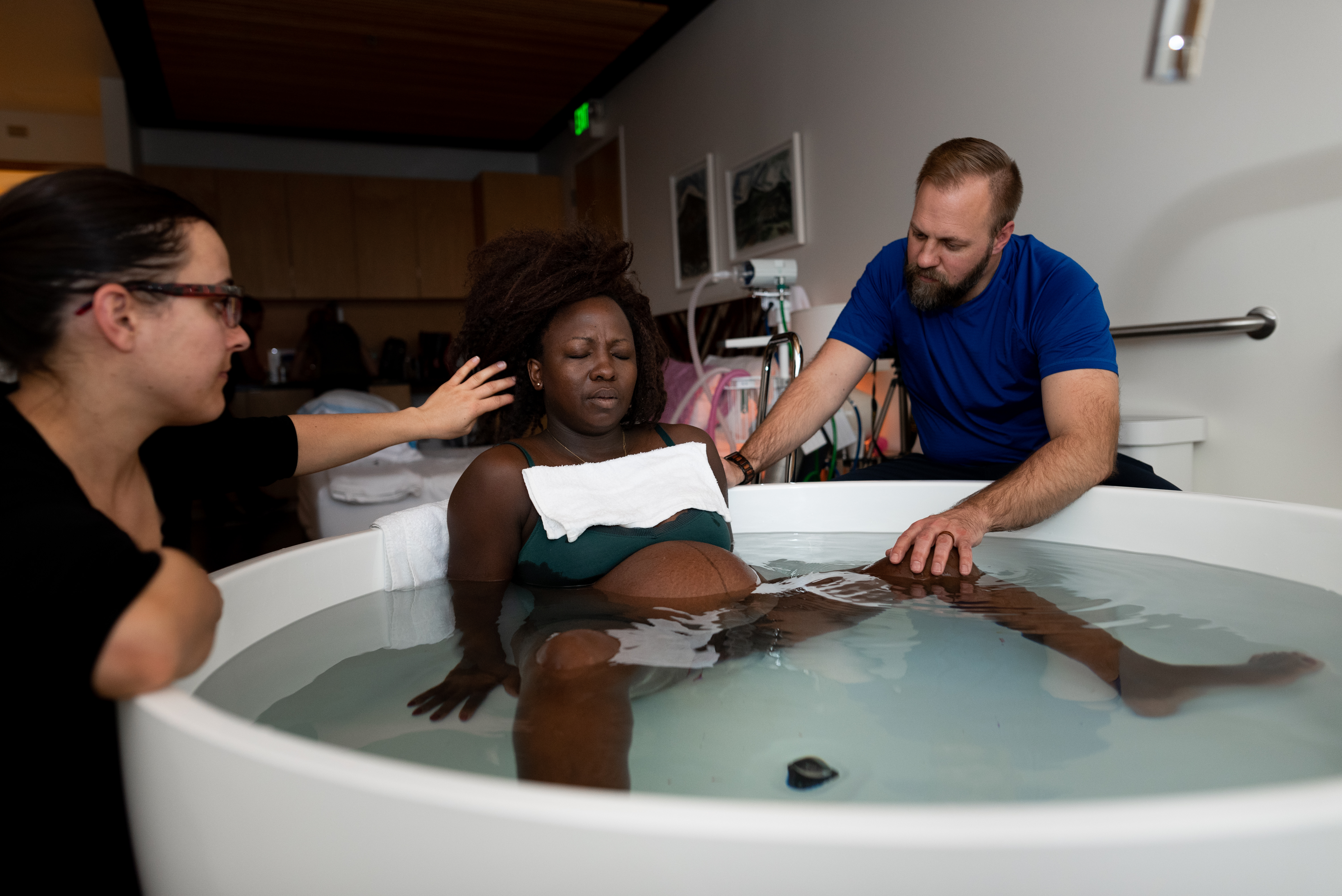 A doula and husband sit near laboring mother while she labors in a bathtub during birth story session