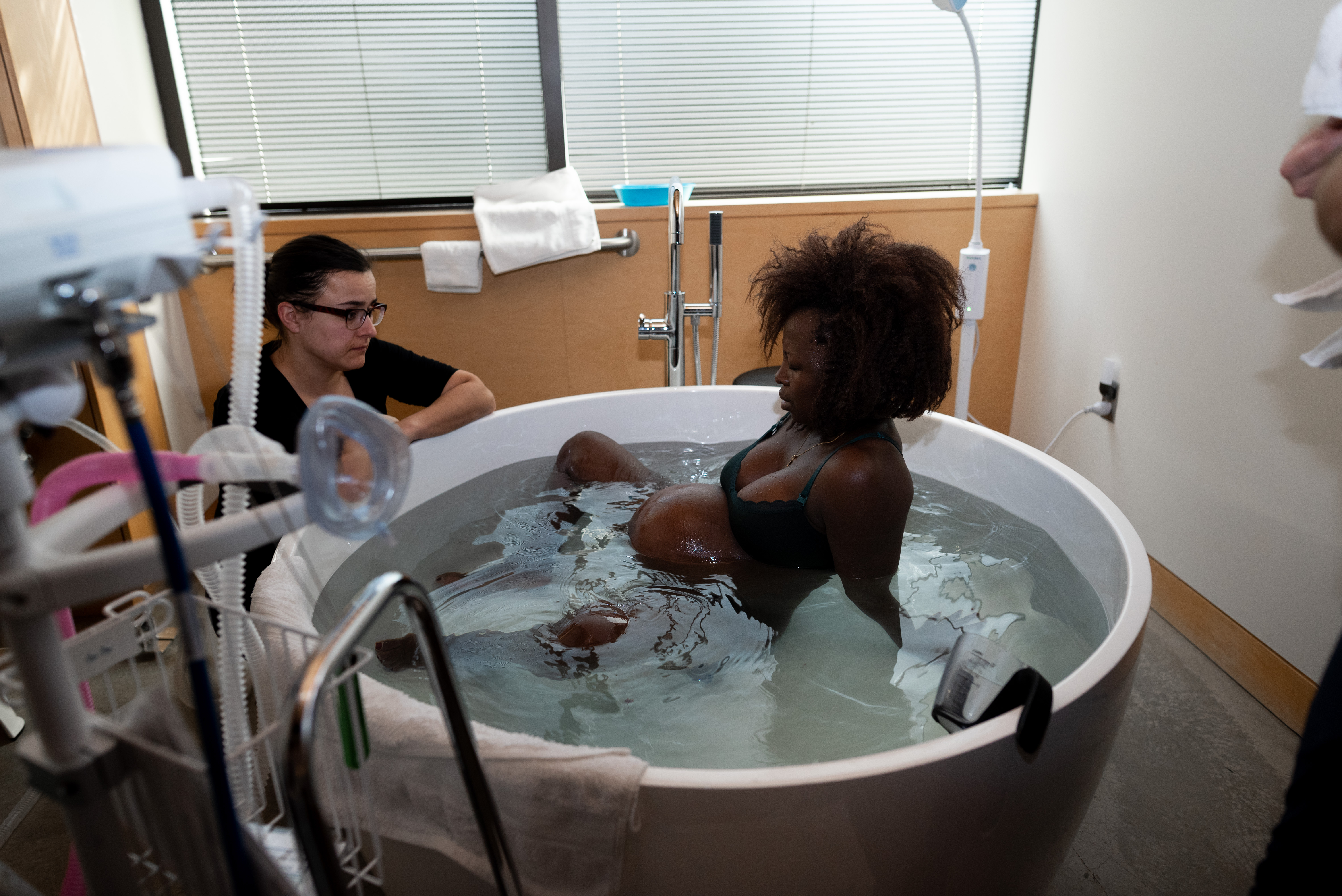 Mother sits in bathtub while she labors during her birth story