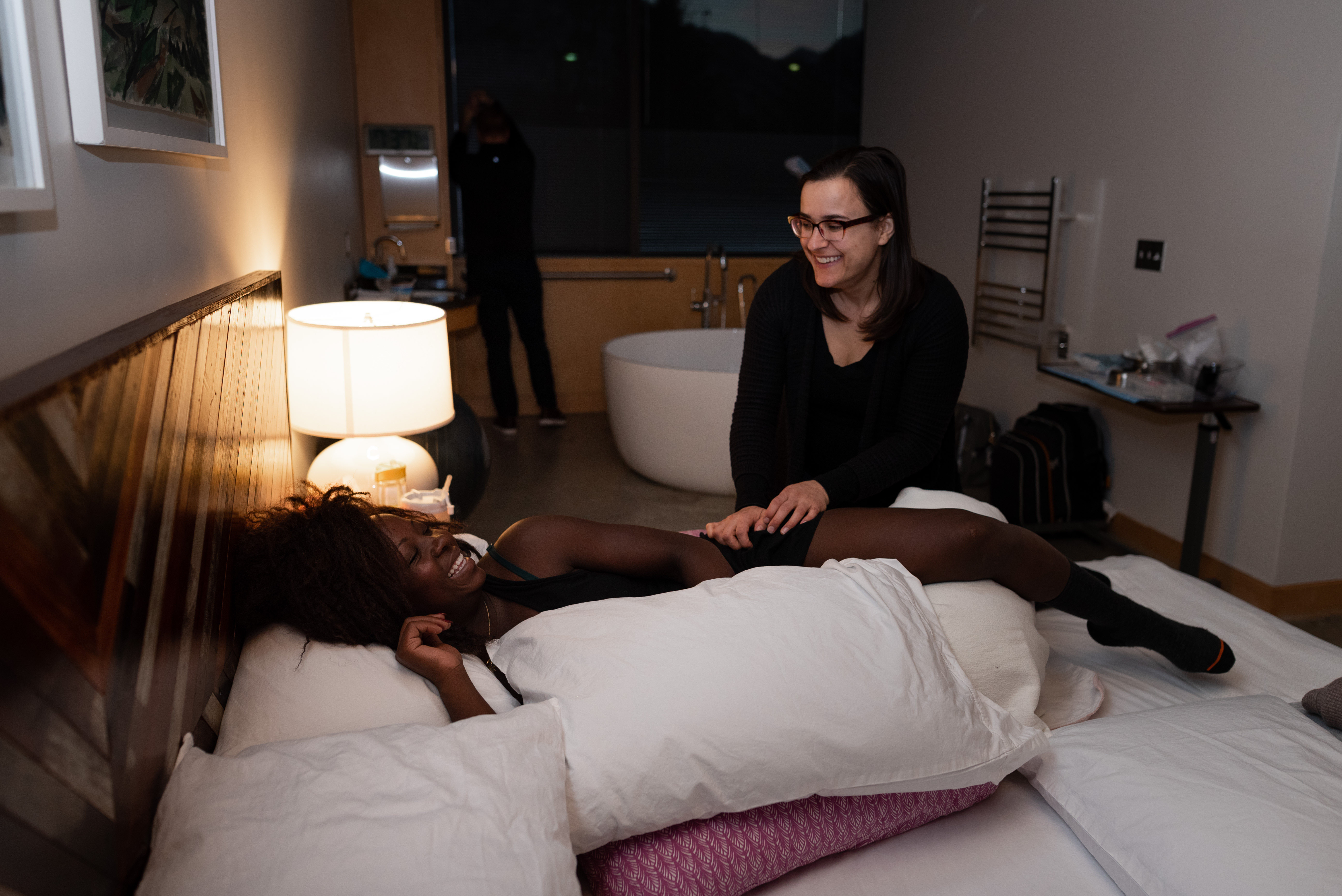 Utah doula smiles at laboring mother while she massages her legs
