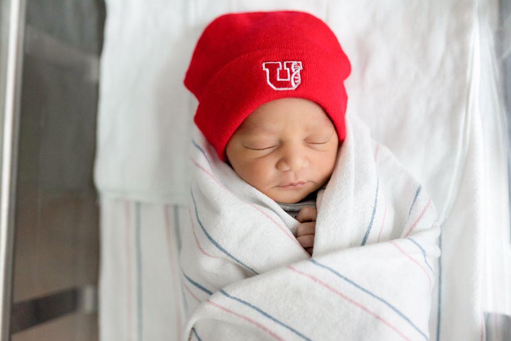 Baby sleeping in bassinet wearing a University of Utah hat