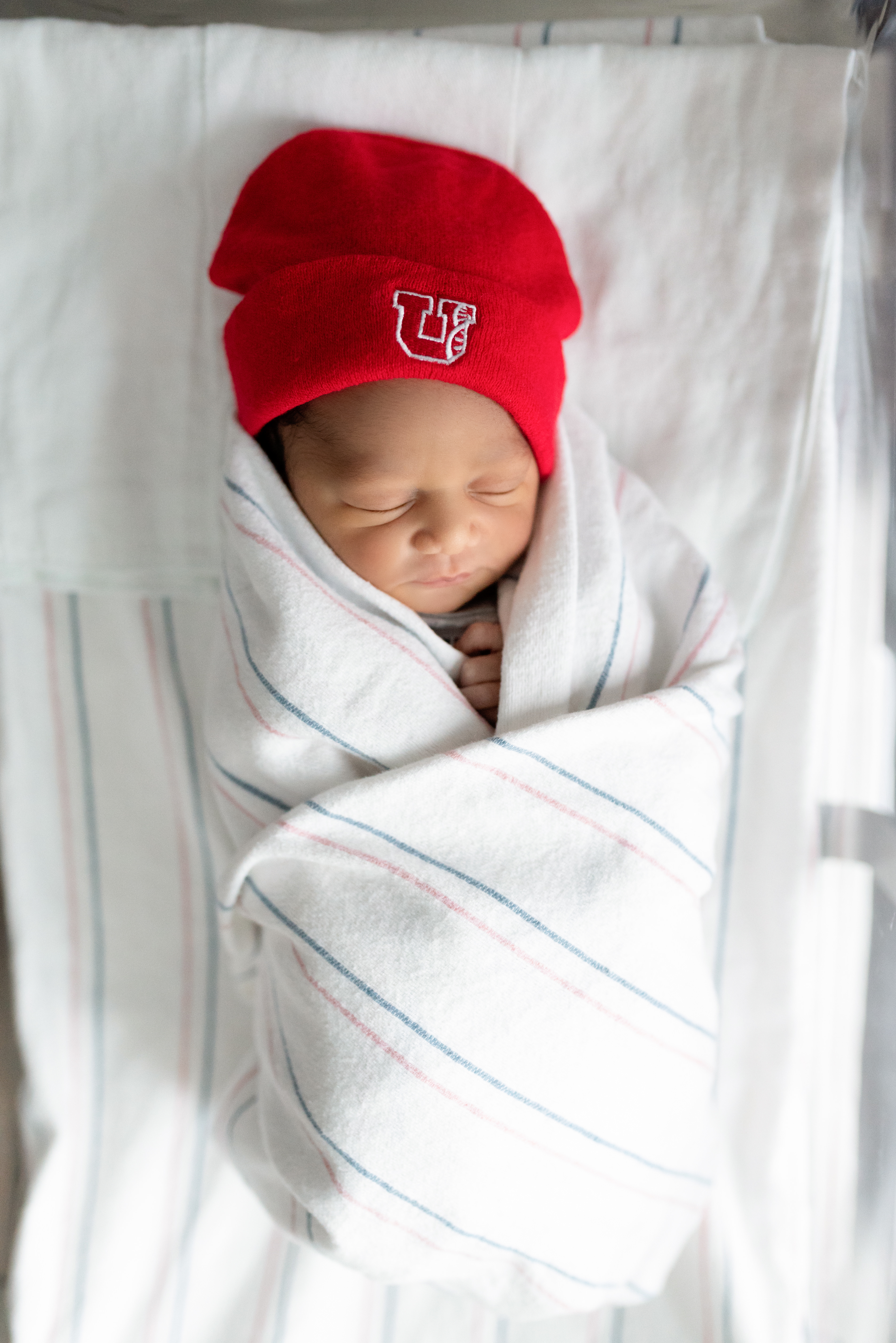 Baby in University of Utah hat sleeps in hospital bassinet during a fresh 48 photography session