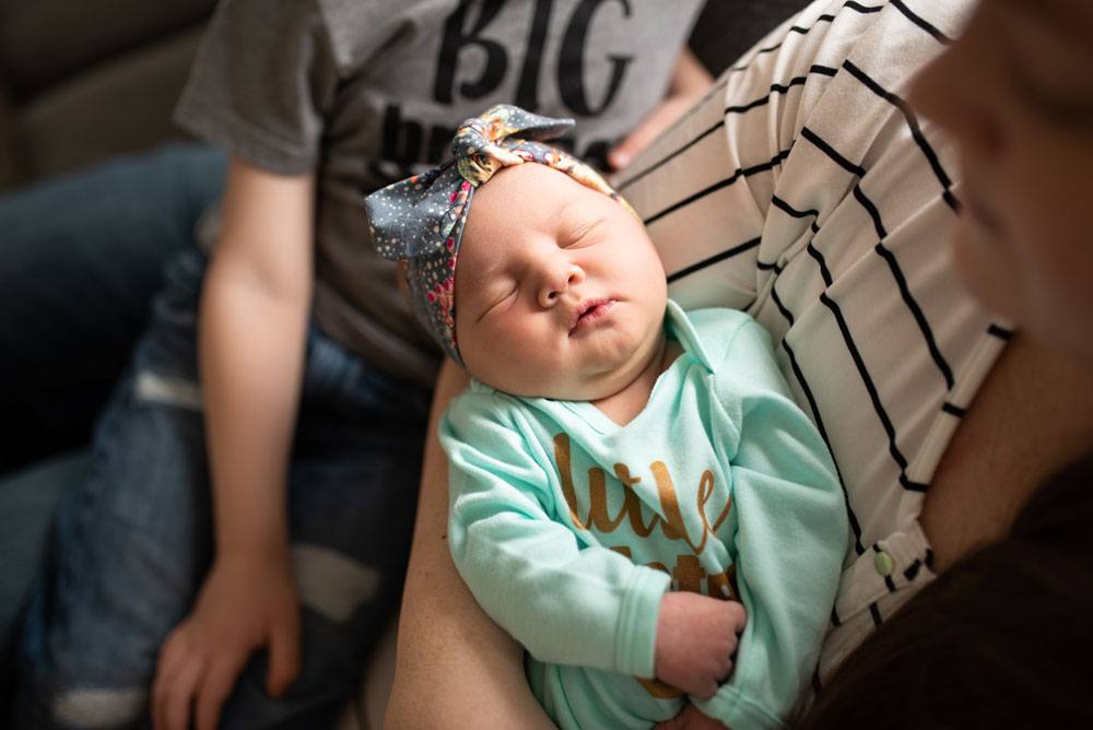 Newborn girl sleeps in her mother's arms during a lifestyle newborn session in Salt Lake City