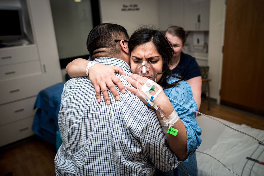 Laboring mother hugs onto dad while experiencing contractions during a birth story session