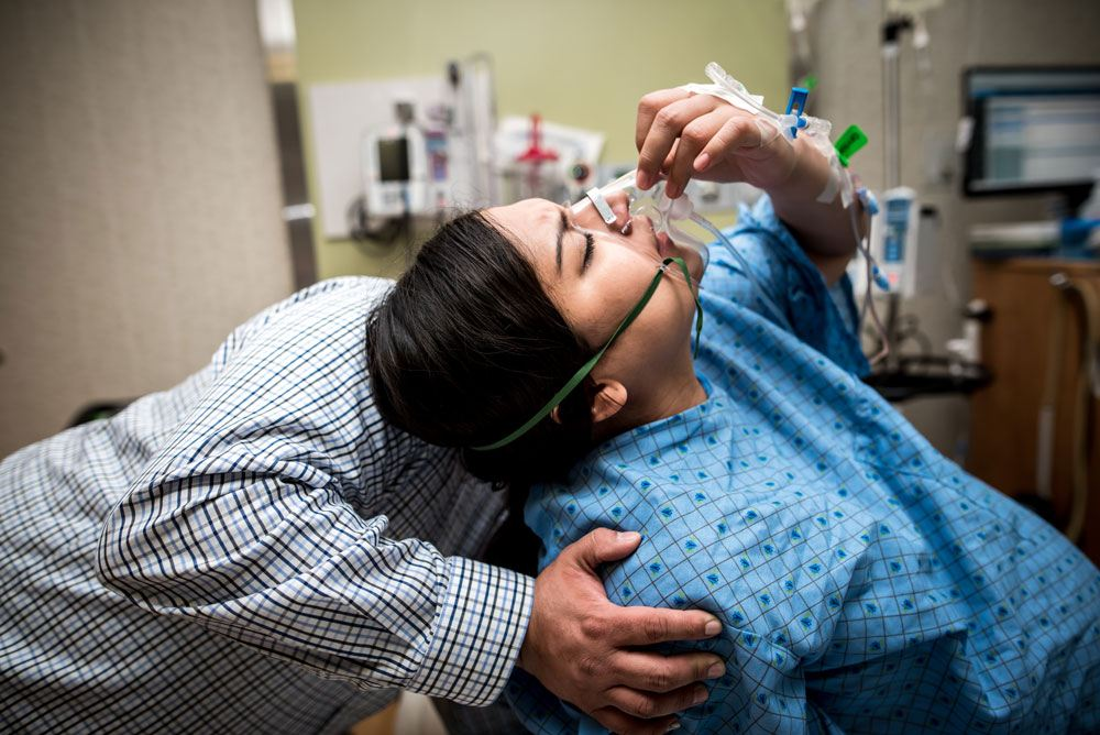 Laboring woman holds oxygen to her face as she prepares to push