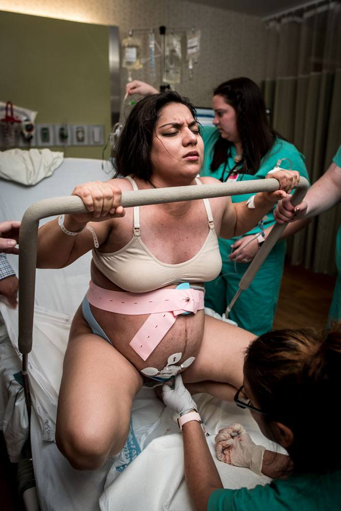 Laboring mother using squat bar while pushing in labor