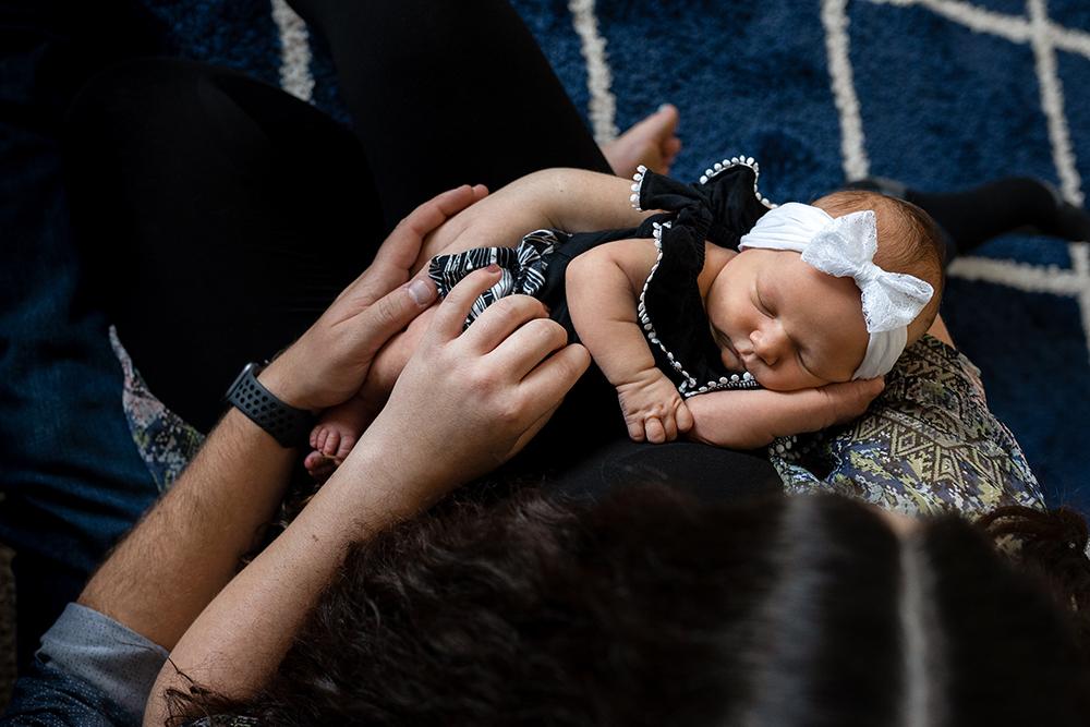 Newborn baby girl sleeps in her parents arms