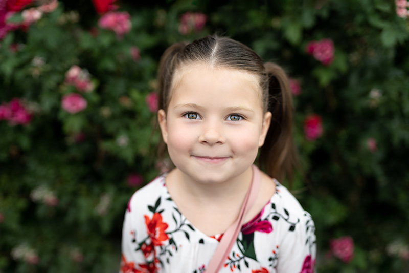 Little girl with pigtails in front of flowers