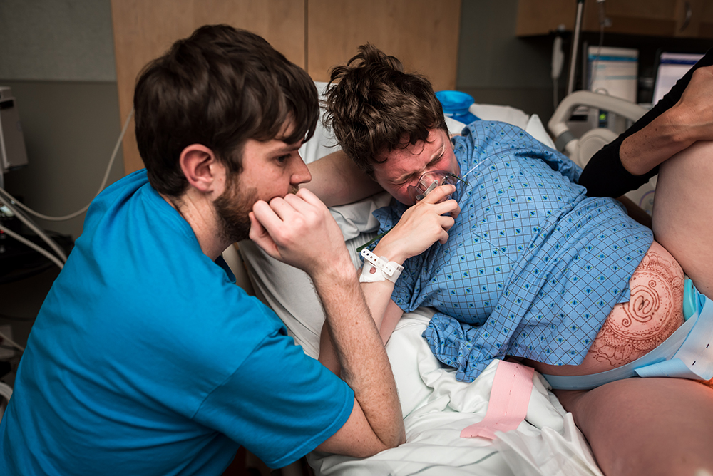Woman pushes during labor during the birth of her newborn son while dad is close by