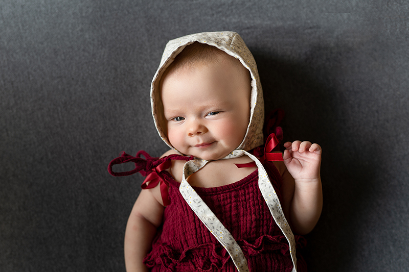 Baby in bonnet and red shirt