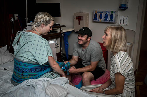 Laboring woman, mom and husband sit in hospital room during labor