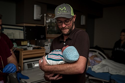New dad holds is son who was just born