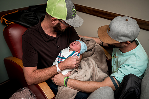 New dads admire their newborn son in hospital chairs