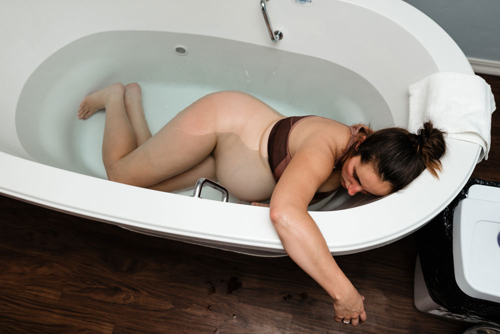 Woman lies in tub during birth story