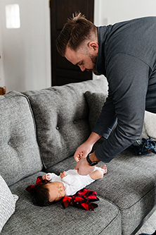 Dad changing newborn baby out of onsie as  he leans over the couch
