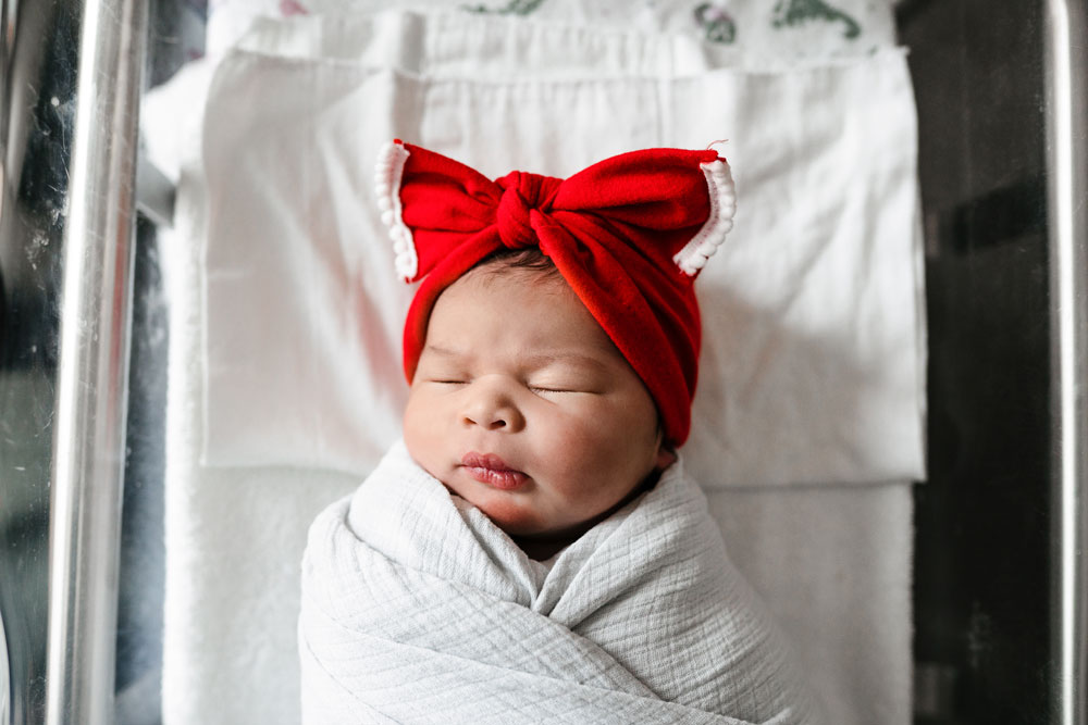 Baby girl sleeps in bassinet at the hospital during fresh 48 session